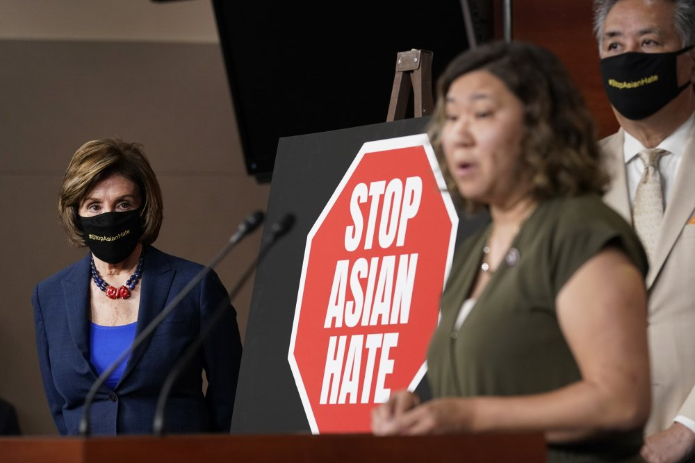 House Speaker Nancy Pelosi of Calif., left, listens as Rep. Grace Meng, D-N.Y., center, speaks during a news conference on Capitol Hill in Washington, Tuesday, May 18, on the COVID-19 Hate Crimes Act. Rep. Mark Takano, D-Calif., listens at right.