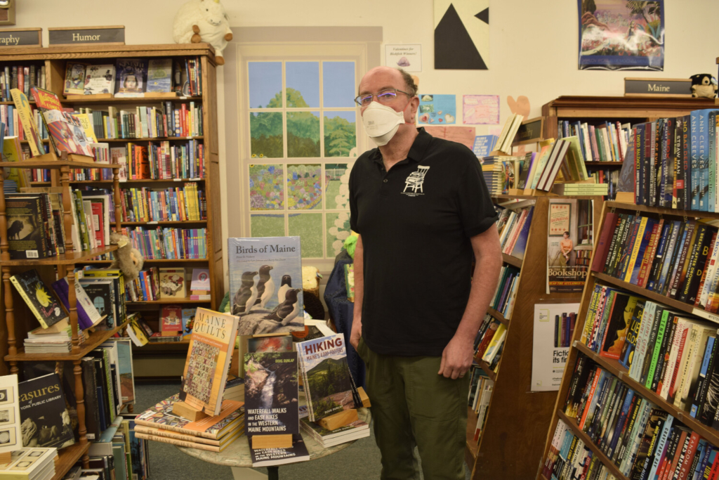 Devaney, Doak & Garrett owner Kenny Brechner stands in front of a display of books about Maine and by Maine authors.