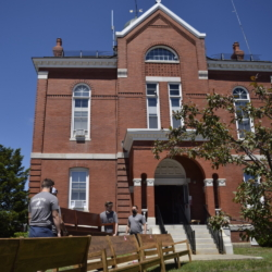 Movers bring in a new cherry-wood stained bench into the Franklin County Superior Court, a red-brick building with white embellishments and big windows. In front of the movers sit benches that are being removed. The old benches are old, worn down, and fading. Behind the courthouse is a bright blue sky without any clouds.