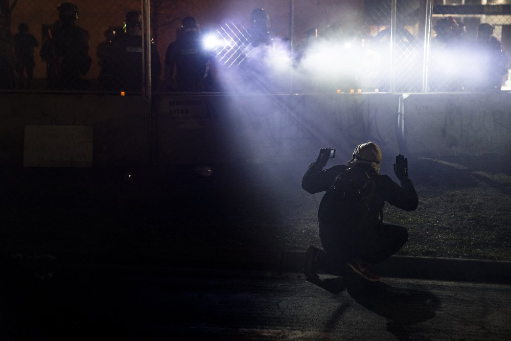 """Police shine lights on a demonstrator with raised hands during a protest outside the Brooklyn Center Police Department in Brooklyn Center, Minn., over the fatal shooting of Daunte Wright, on April 14. The American Civil Liberties Union of Minnesota called the proposal """"an important first move"""" in changing policing."""
