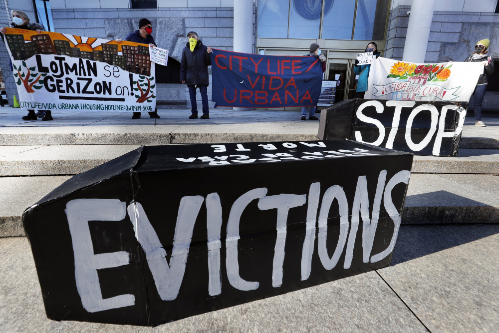 Demonstrators hold signs in front of the Edward W. Brooke Courthouse in Boston on Jan. 13, 2021.