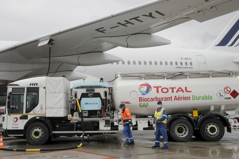 Workers refuel an Airbus A350 with sustainable aviation fuel at Charles de Gaulle airport on Tuesday. Air France-KLM is aiming to make 5 percent of its fuel sustainable by 2030.