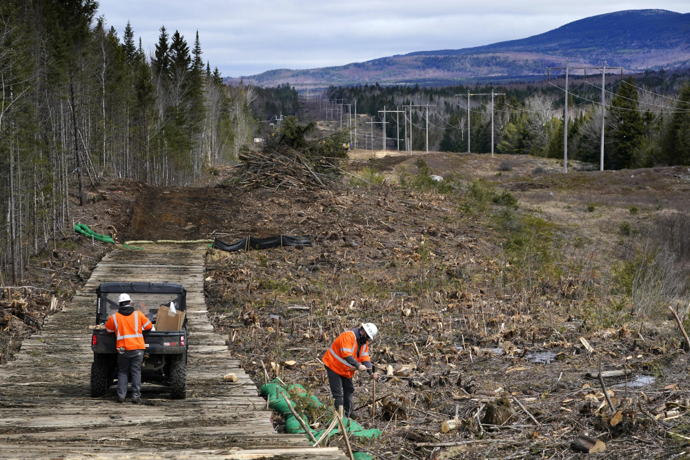 Workers for Northern Clearing pound stakes to mark land on an existing Central Maine Power power line corridor that has been recently widened to make way for new utility poles, near Bingham in April.