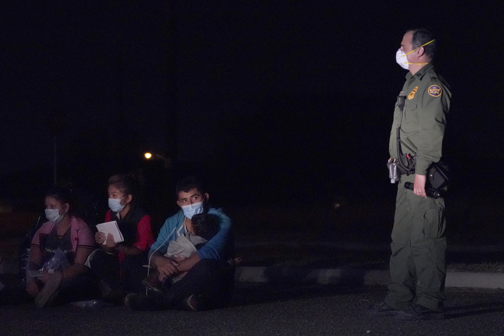 Migrants wait with at a U.S. Customs and Border Protection agent at an intake area after crossing the U.S.-Mexico border on March 24 in Roma, Texas. A new report found at least 348 cases in which Immigration and Customs Enforcement had no records showing migrants wanted to leave their children in the U.S.
