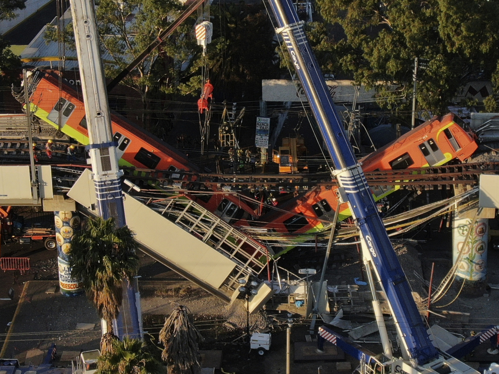 An aerial view of subway cars dangle at an angle from a collapsed elevated section of the metro, in Mexico City, Tuesday, May 4, 2021. The elevated section collapsed late Monday killing at least 23 people and injuring at least 79, city officials said.