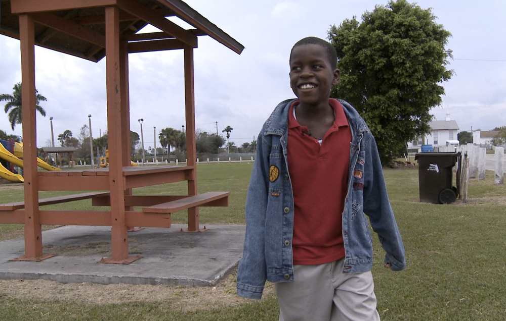 Then-10-year-old Damon Weaver walks in a park near his home in Pahokee, Fla., in 2009. Weaver who gained national acclaim when he interviewed President Barack Obama at the White House that year, has died of natural causes, his family says.   Lynne Sladky/Associated Press