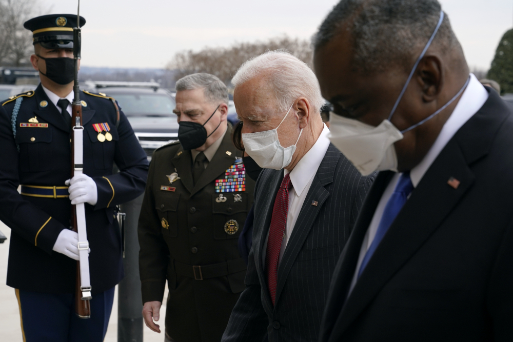 President Biden walks with Joint Chiefs Chairman Gen. Mark Milley, second from left, and Defense Secretary Lloyd Austin as he arrives at the Pentagon in February. Milley said he has shifted his thinking on policy changes regarding sexual assault in the military in part because he is concerned by indications of a lack of confidence by junior enlisted service members in the fairness of sexual assault case outcomes.