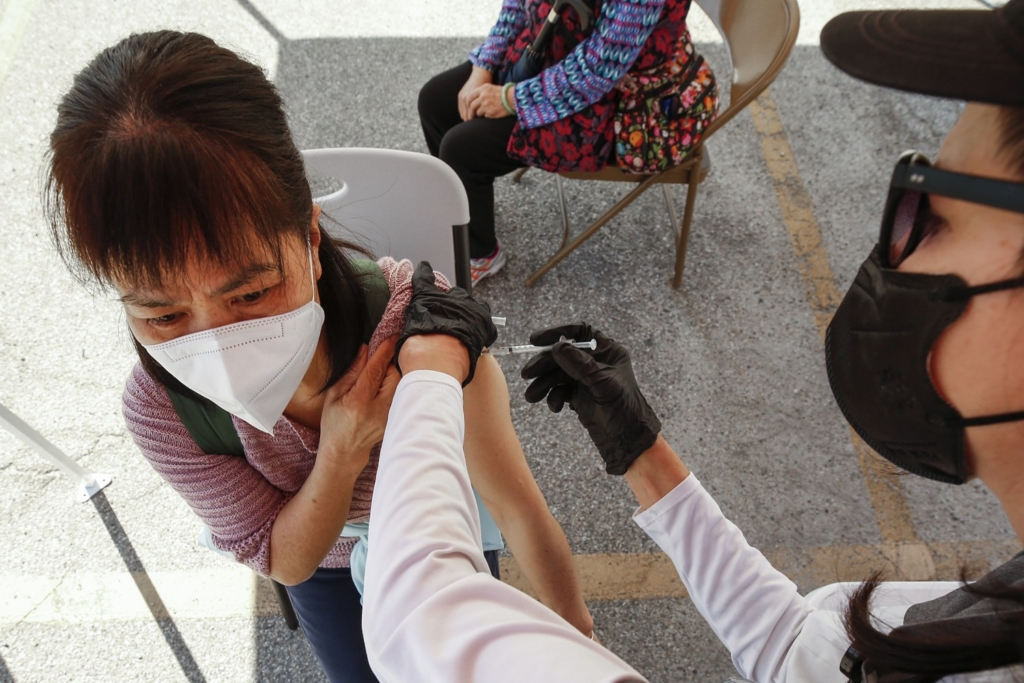 A woman receives a COVID-19 vaccination at a mobile clinic in Los Angeles' Chinatown. Studies have offered reassurance that existing vaccines work well against the two most dominant strains in California.