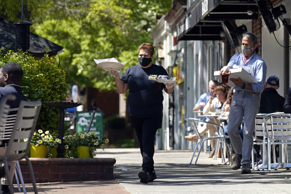 A member of the wait staff takes food to outdoor diners at the Mediterranean Deli restaurant in Chapel Hill, N.C., Friday, April 16. Thousands of restaurants and bars decimated by COVID-19 have a better chance at survival as the government begins handing out $28.6 billion in grants.