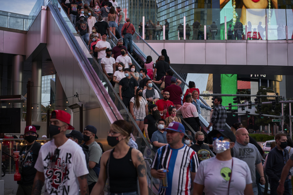 People ride an escalator along the Las Vegas Strip on April 24. The city is bustling again after casino capacity limits were raised to 80 percent.