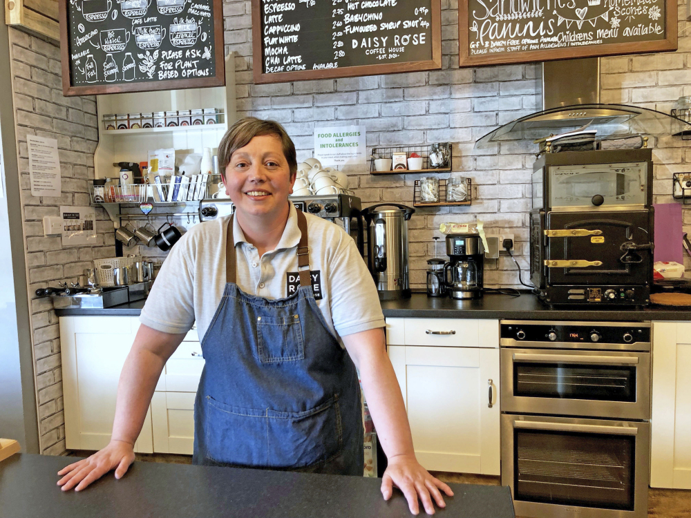 Caroline Atkinson, owner of the Rose Coffee House, prepares to reopen, in Belmont, Durham, England. On Monday, people in England will be able to eat a restaurant meal indoors, drink inside a pub and visit one another's homes for the first time in months.