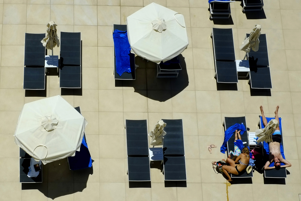 A family gathers at the pool of Nissi Blue hotel in the resort of Ayia Napa, in the eastern Mediterranean island of Cyprus, on Saturday. Cypriot hotel and other tourism-related business owners say they'd like to see the COVID-19 pandemic-induced uncertainty over travel bookings  wind down by July.