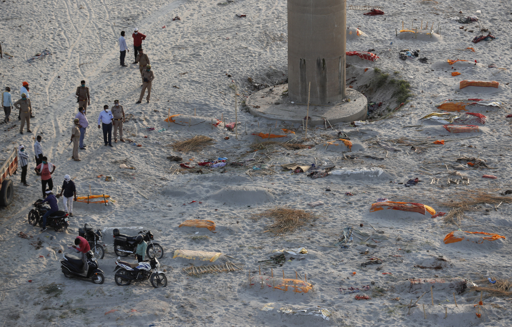 Policemen stand next to the bodies buried in shallow graves on the banks of Ganges river in Prayagraj, India, Saturday.