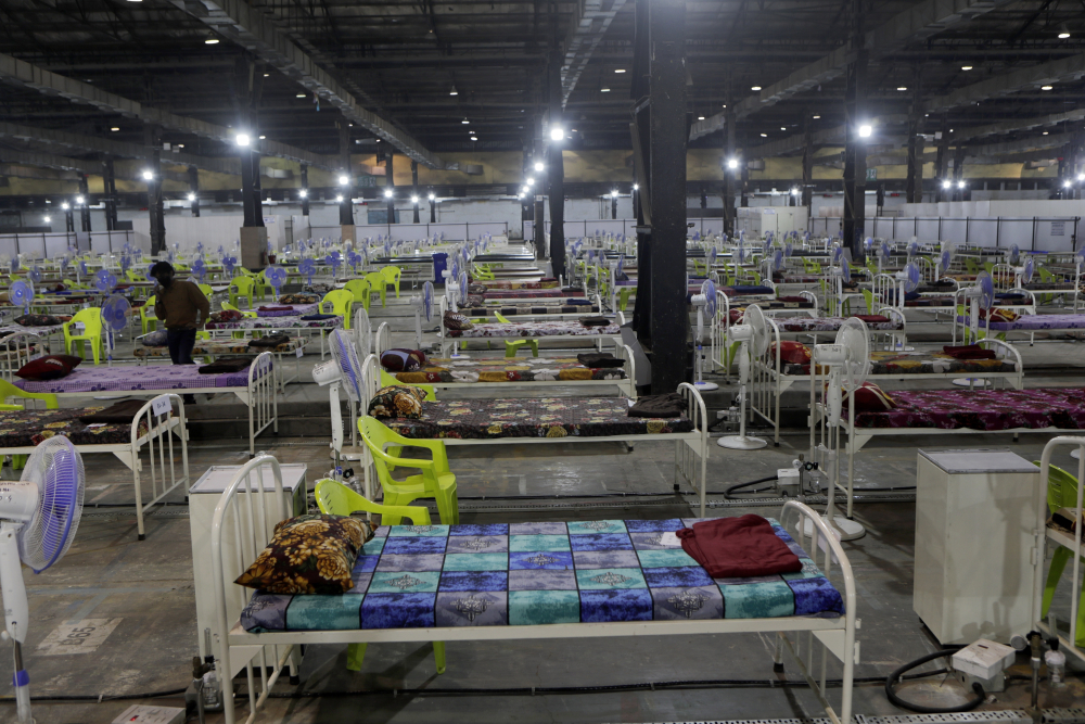 Newly arranged beds lie inside a COVID-19 treatment center set up for emergencies in the wake of spike in the numbers of positive coronavirus cases in Mumbai, India, Thursday, May 6. Infections in India hit another grim daily record on Thursday as demand for medical oxygen jumped seven-fold and the government denied reports that it was slow in distributing life-saving supplies from abroad.