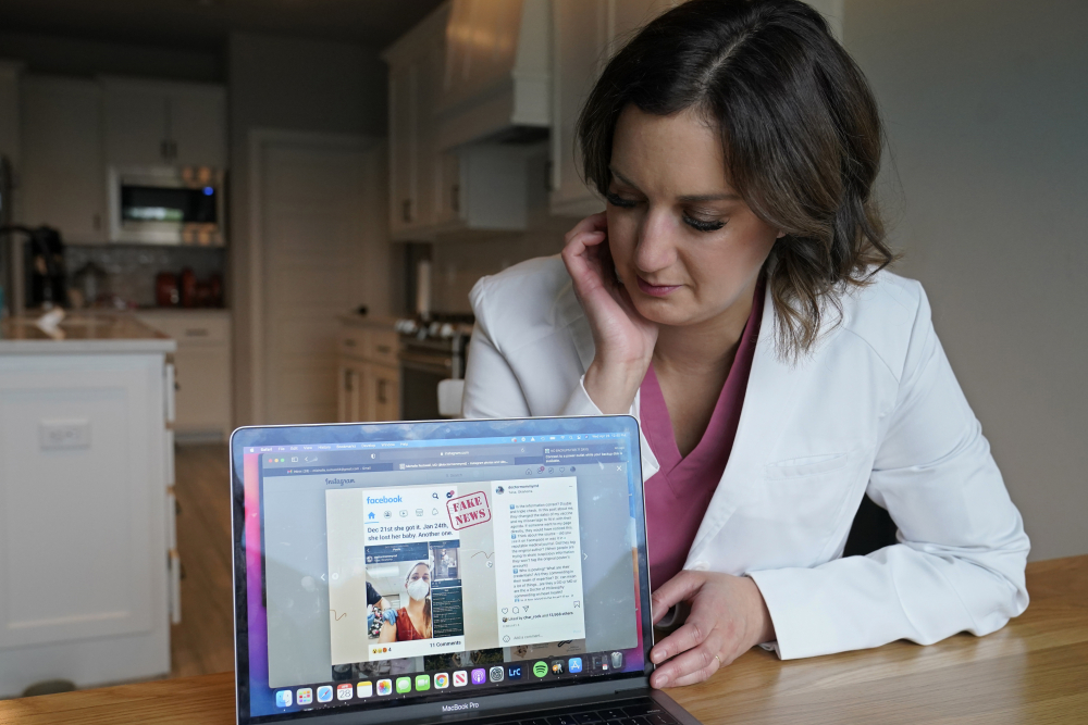 Dr. Michelle Rockwell, who was targeted by vaccine opponents after she posted about her miscarriage online, looks at her Instagram page with her hijacked post marked as fake news during an interview at her home Wednesday, April 28, 2021, in Jenks, Okla.