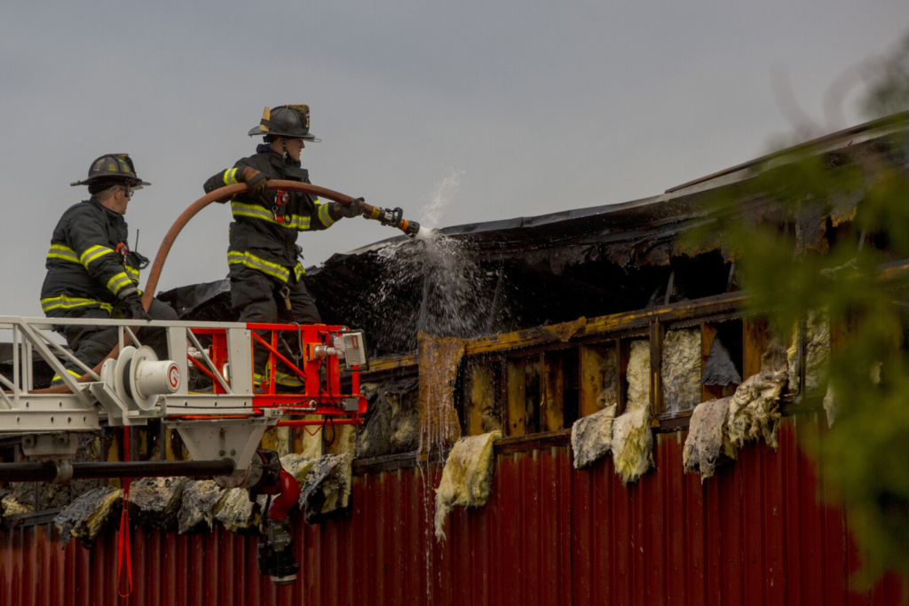 Firefighters cleanup after an early morning fire at 160 Presumpscot Street in Portland on Friday.