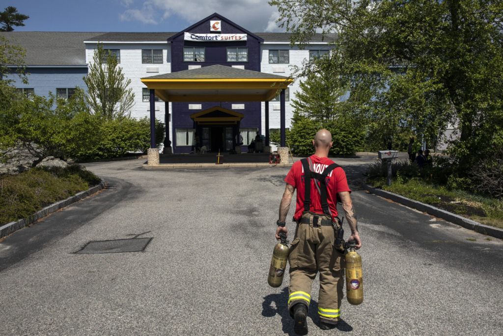 FREEPORT, ME - JUNE 29: A Yarmouth firefighter carries two SCBA bottles in for firefighters who were entering the Comfort Suites after it was evacuated due to high carbon monoxide levels inside the hotel in Freeport on Tuesday, June 29, 2021. A water heater malfunction is believed to have been the cause of the leak that sent three people to the hospital. (Staff photo by Brianna Soukup/Staff Photographer)