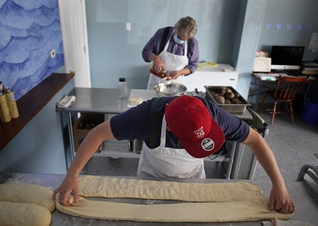 Graeme Miller, owner of BenReuben's Knishery in South Portland, stretches out dough for knishes while his father Richard, a retired pediatrician who is now working for his son, combines ingredients for rugelach.