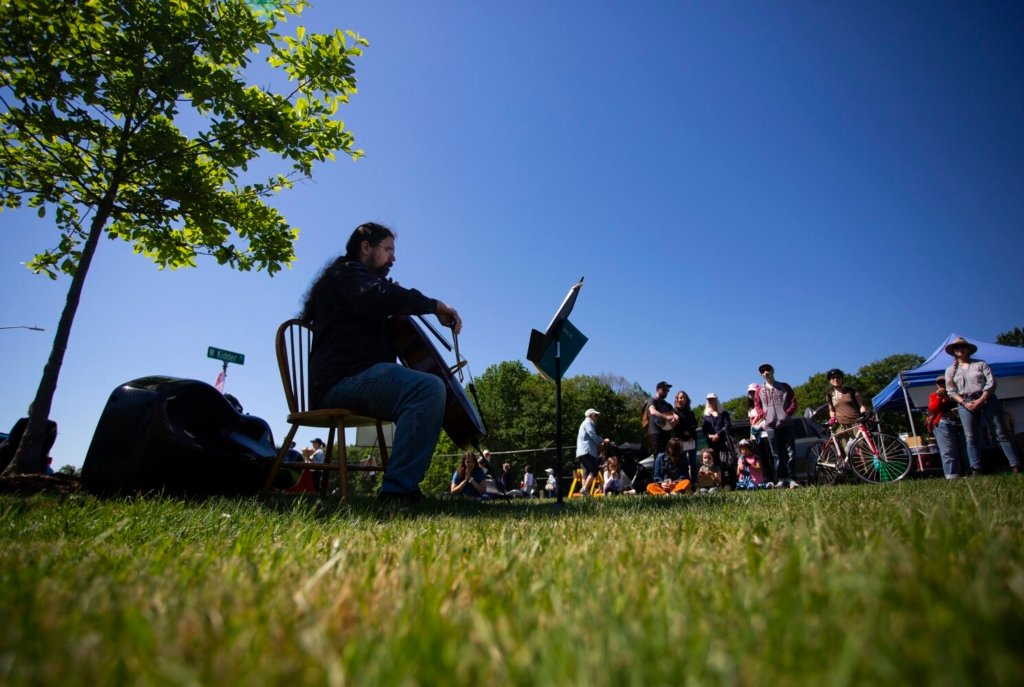 John Ott of Portland sits in the shade of a tree as he plays the cello at a farmers market in Payson Park on Saturday. The performance was part of the Portland Bach Experience.