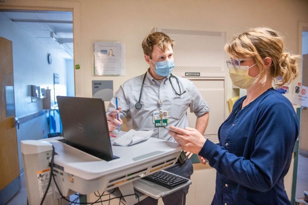 Dr. Zack Mueller goes over rounds Thursday with Rachel Vendenhuevel, RN, at Central Maine Medical Center in Lewiston. Mueller is a hospitalist, who has spent much of the past year caring for COVID patients.