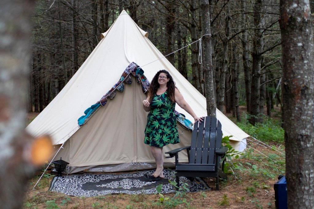 """Trinity Madison stands before one of the """"glamping"""" tents on her 17-acre site. Maine officials say such businesses are legal but must be careful not to run afoul of state law."""