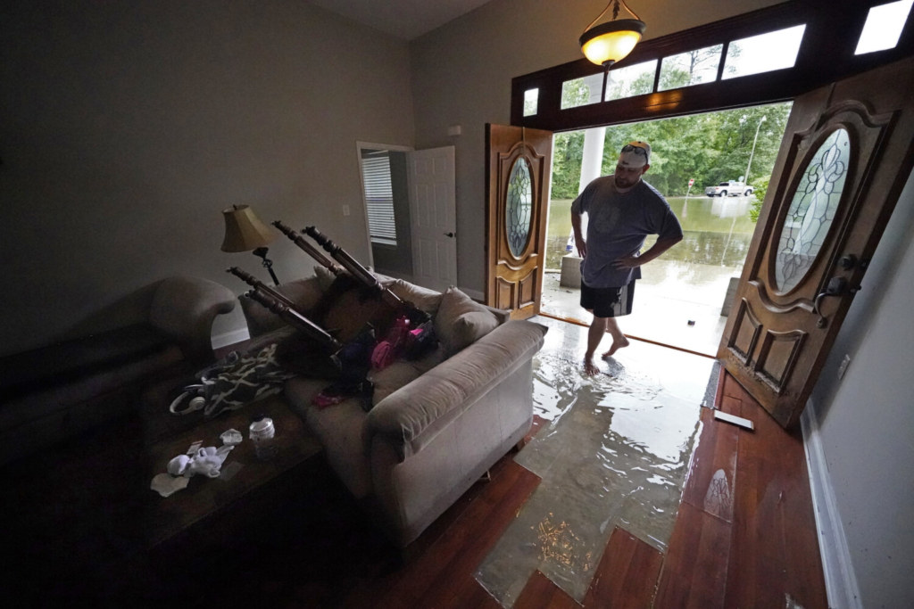 Danny Gonzales surveys his flooded house after Tropical Storm Claudette passed through, in Slidell, La., on Saturday.