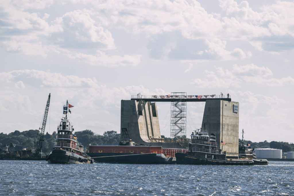 """A 5,000-ton concrete entrance structure is towed out of the harbor Sunday in Portland. The structure, built by Cianbro in Portland, will be used by the Navy at the """"Superflood Basin"""" project at the Portsmouth Naval Shipyard in Kittery. The structure will allow submarines easier access to dry docks."""