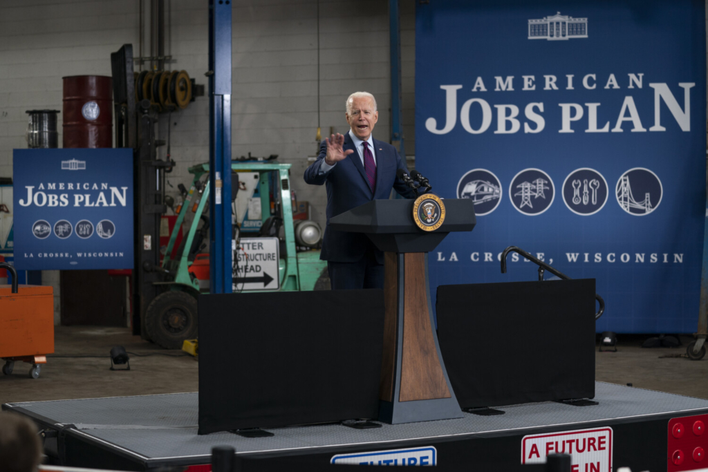 """President Biden speaks about infrastructure spending at the La Crosse Municipal Transit Authority on Tuesday in La Crosse, Wis. """"This is a blue-collar blueprint to rebuild America,"""" he said."""