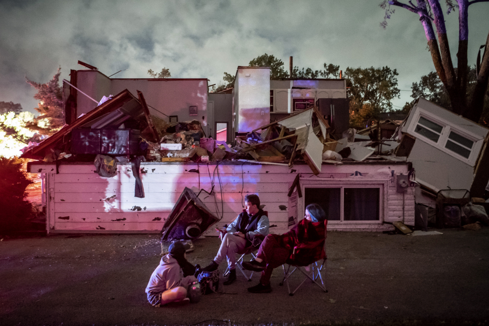 Bridget Casey sits in the driveway of her severely damaged home with her son Nate, 16, and daughter Marion, 14, after a tornado swept through the area in Woodridge, Ill., early Monday morning.