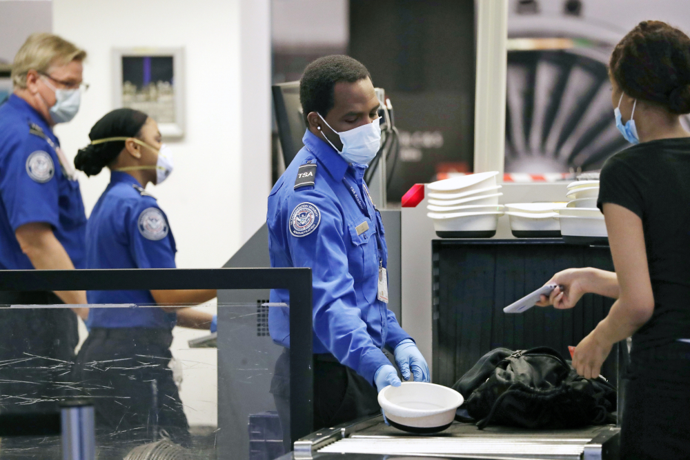 Transportation Security Administration officers wear protective masks at a security screening area at Seattle-Tacoma International Airport in SeaTac, Wash. on May 18, 2020.