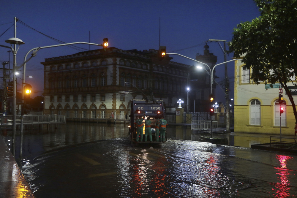 City workers ride on the back of a garbage truck navigating through a street flooded by the Negro River, in downtown Manaus, Amazonas state, Brazil, on Tuesday.