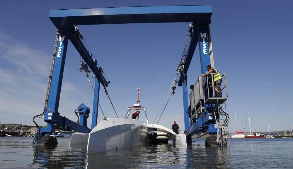 Technicians lower the so-called Mayflower Autonomous Ship into the water at its launch site for its first outing on water since being built in Turnchapel, England, in September 2020. The ship began a trans-Atlantic trip Tuesday, but the voyage was aborted when a mechanical problem developed.