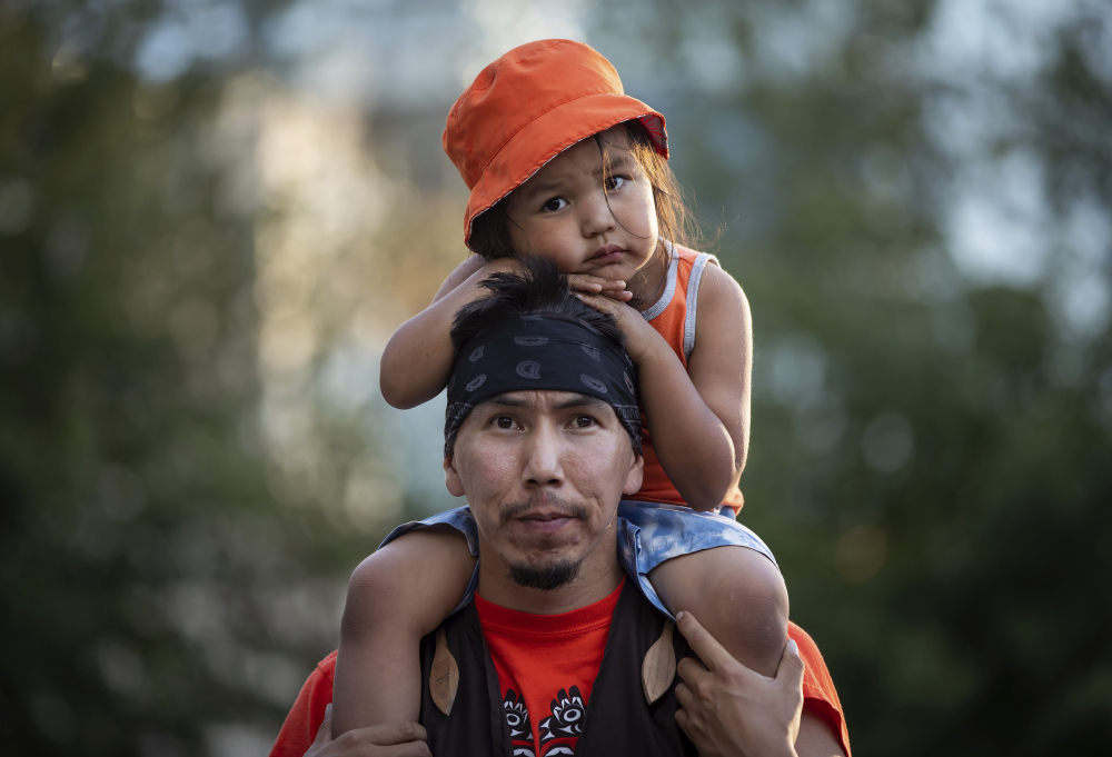 Cowichan Tribe member Benny George holds his child Bowie, 3, on his shoulders as they listen during a ceremony and vigil for the 215 children whose remains were found buried at the former Kamloops Indian Residential School, in Vancouver, British Columbia, on National Indigenous Peoples Day on Monday.