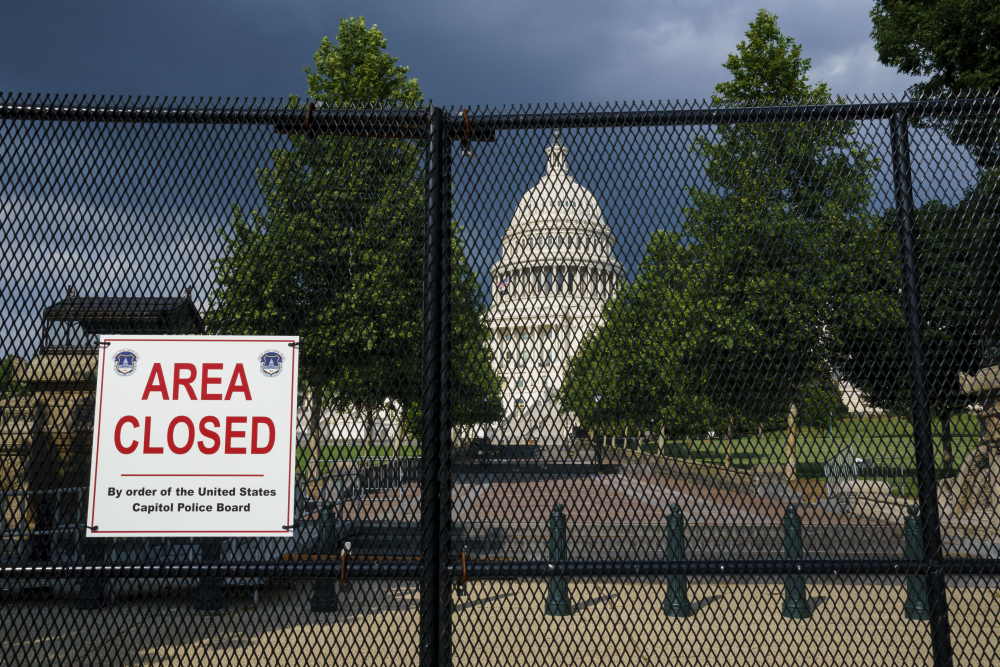 The U.S. Capitol is seen under dark skies in Washington on Tuesday. Barriers remain six months after the Jan. 6 attack.