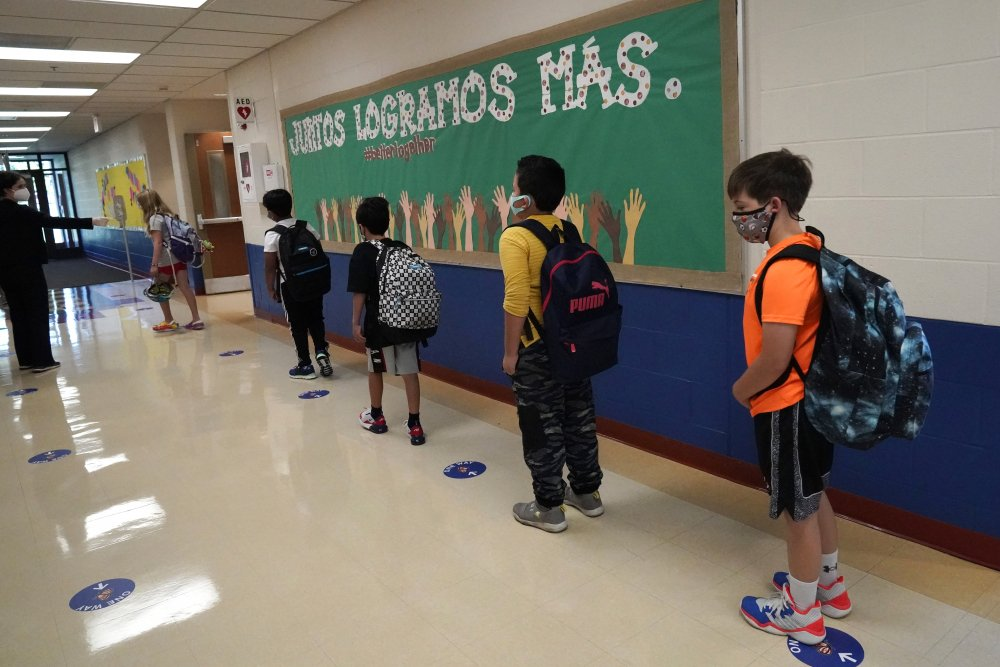 Students keep social distance as they walk to their classroom Sept. 3, 2020, in Highwood, Ill., part of the North Shore school district.