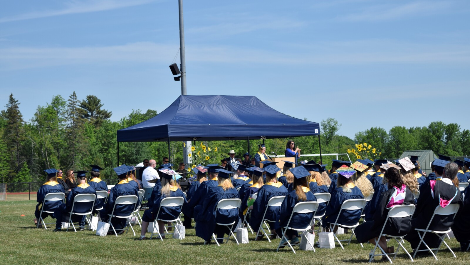 In the foreground, high school graduates sit in blue robes and caps. Some of the caps are decorated with phrases, LGBTQ rainbow-flag colors, and personal pictures. In the background, a student in a robe and cap stands on stage speaking into a microphone. Next to the student is an ASL interpreter.