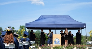 """In the foreground, high school graduates sit facing a stage wearing decorated graduation caps on their heads. In the background, a student walks across a stage in a blue graduation robe and cap holding a diploma. The student is fist bumping a man in a black robe wearing sunglasses. He is surrounded by other school administrators in black robes who are clapping. The stage has a podium on it with the Mt. Blue """"cougars"""" logo on it."""