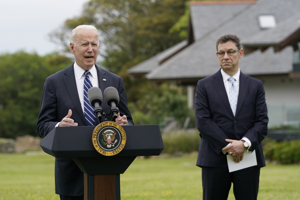 President Biden speaks about his administration's global COVID-19 vaccination efforts ahead of the G-7 summit, Thursday in St. Ives, England. Pfizer CEO Albert Bourla listens at right.