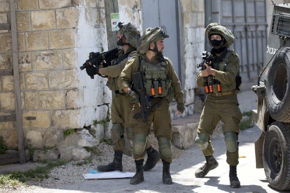 Israeli soldiers patrol after a soldier was killed when a rock thrown off a rooftop struck him in the head during an arrest raid, in the village of Yabad near the West Bank city of Jenin, in May 2020. The Israeli military says it is reining in a controversial practice of conducting late-night raids of Palestinian homes in the West Bank.