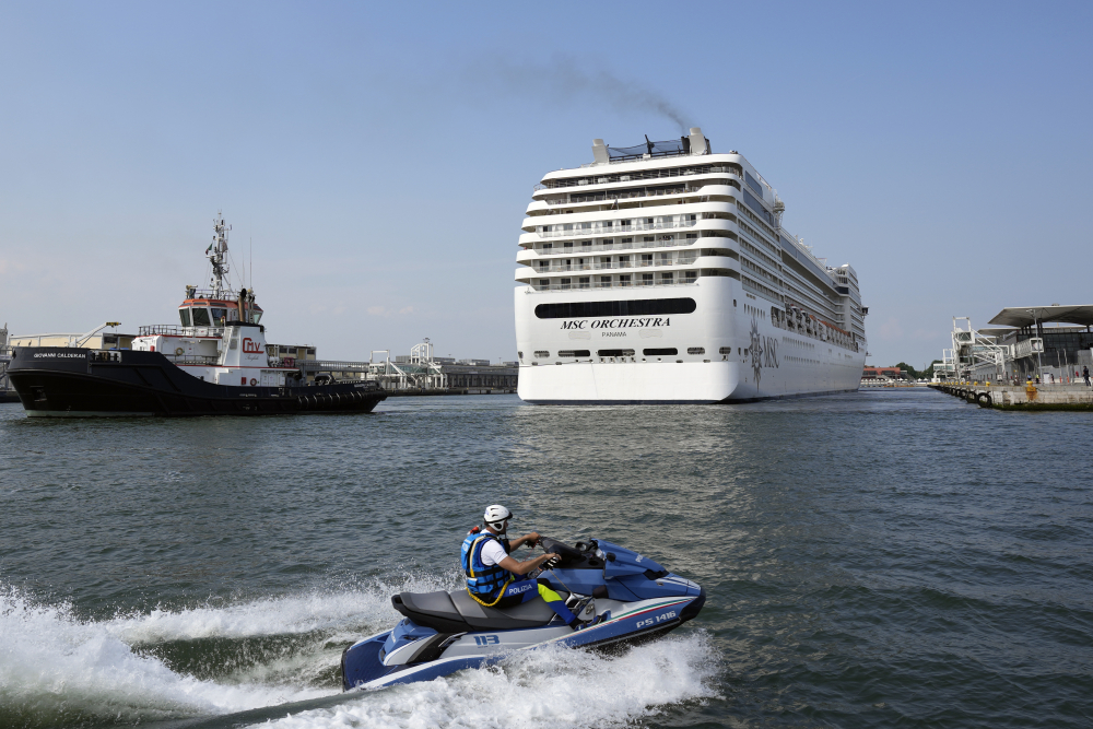 The the 92,409-ton, 16-deck MSC Orchestra cruise ship exits the lagoon as it leaves Venice, Italy, on Saturday. Activists demandithat the enormous ships be permanently rerouted out the fragile lagoon, especially Giudecca Canal through the city's historic center, due to environmental and safety risks.
