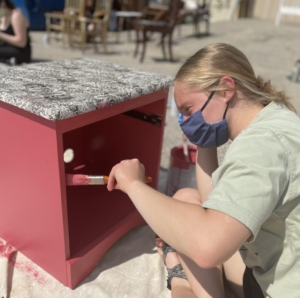 Kennebunk High School senior Phebe Grant paints a cabinet to be sold at Habitat of Humanity York County's Re-Store as part of a senior project.jpg