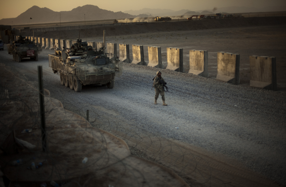 U.S. soldiers from the 5th Striker Brigades walk next to armored vehicles as they arrive at their base Aug. 8, 2009, on the outskirts of Spin Boldak, about 63 miles southeast of Kandahar, Afghanistan.