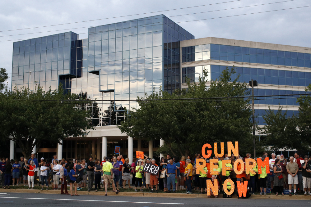People gather at a vigil for recent victims of gun violence outside the National Rifle Association's headquarters building in Fairfax, Va., in August 2019. While the battle over gun rights is shifting from Washington to the states, the NRA's message has become so solidified in the Republican political fabric that it's self-sustaining, even if the gun rights organization that led the way ceases to exist, leaders on both sides say.