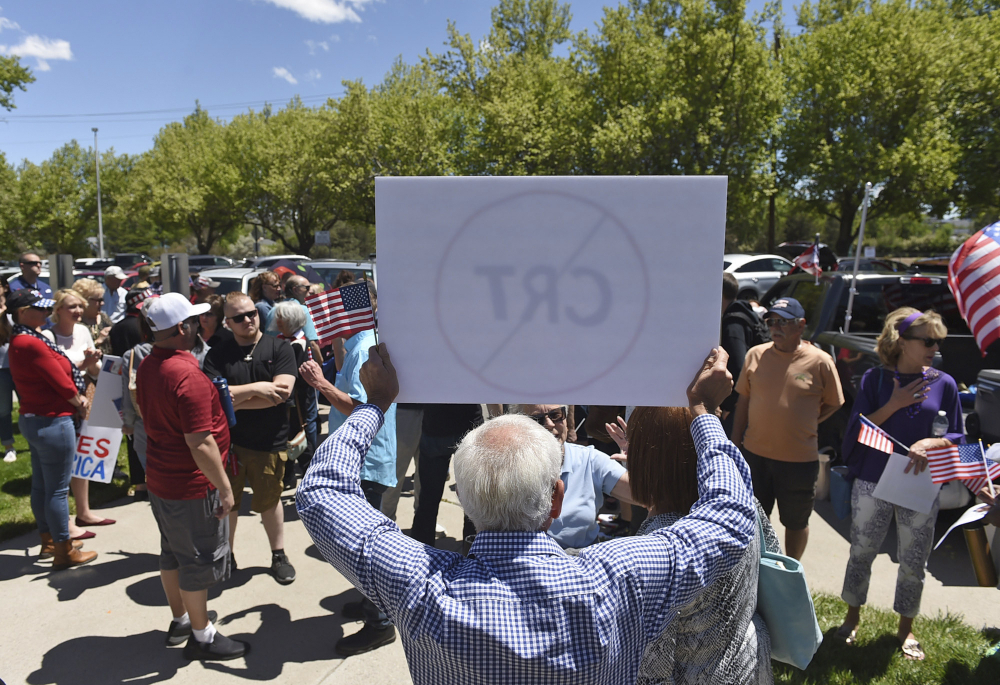 A man holds up a sign against Critical Race Theory during a protest outside a Washoe County School District board meeting on May 25 in Reno, Nev.