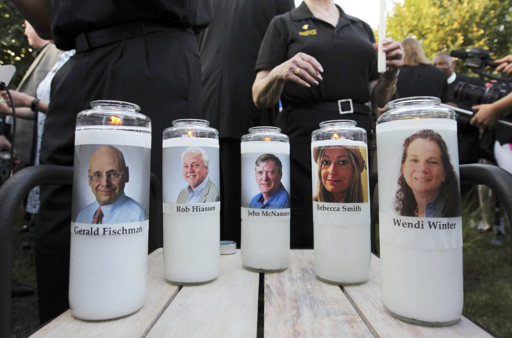 In this June 29, 2018, file photo, photos of five employees of the Capital Gazette newspaper adorn candles during a vigil across the street from where they were slain in the newsroom in Annapolis, Md.