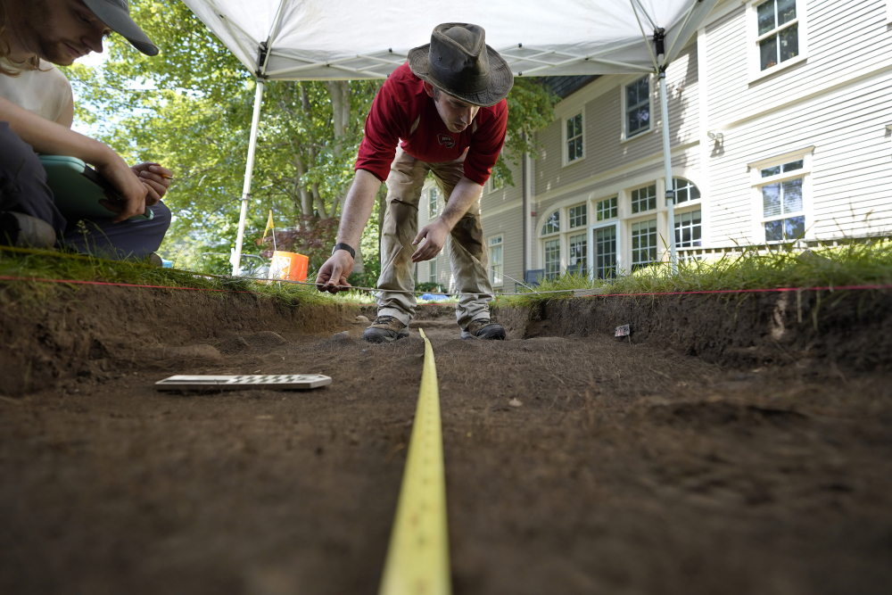 University of Massachusetts Boston graduate students Sean Fairweather, of Watertown, Mass., left, and Alex Patterson, of Quincy, Mass., right, use measuring instruments while mapping an excavation site Wednesday on Cole's Hill in Plymouth, Mass.