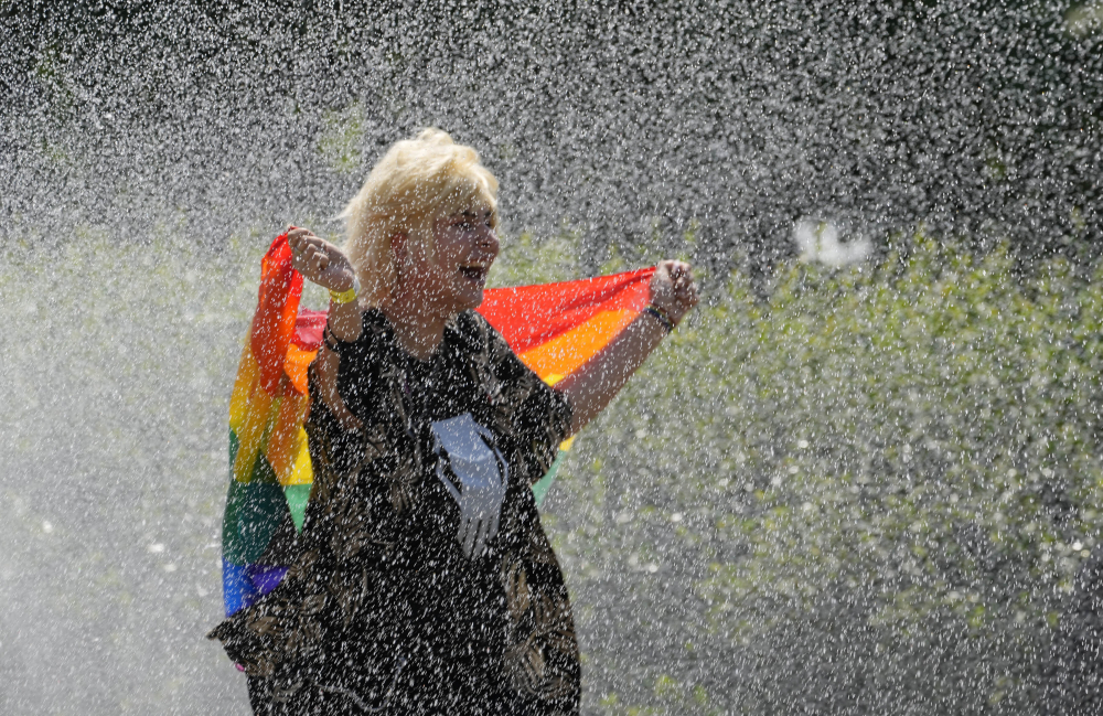 A woman with a rainbow flag cools off in a sprinkler ahead of the Equality Parade, the largest LGBT pride parade in centralcEurope, in Warsaw, Poland, on Saturday.