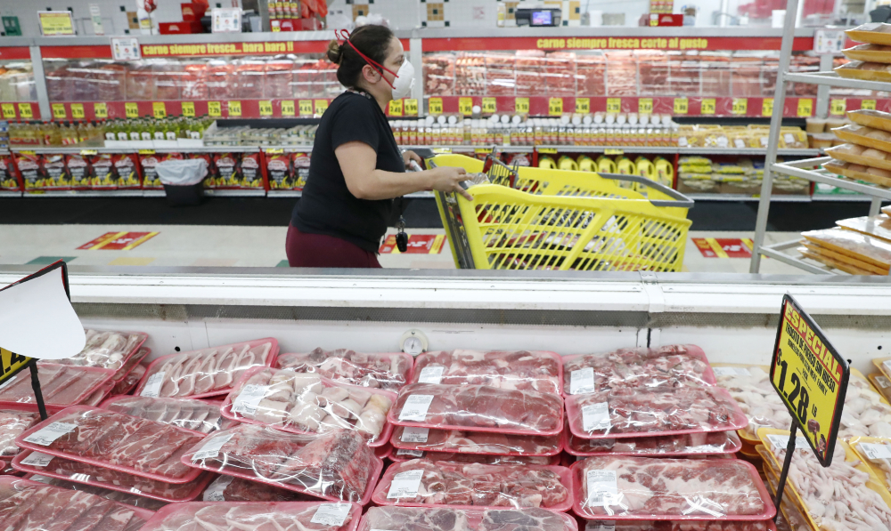 Ashopper wears a mask as she walks through the meat products at a grocery store in Dallas on April 29, 2020.  Wholesale prices, boosted by rising food costs, increased 0.8% in May 2021, and are up by a record amount over the past year.