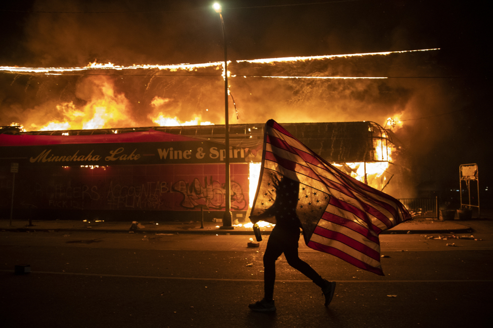 A protester carries a U.S. flag upside down, a sign of distress, next to a burning building, May 28, 2020, in Minneapolis. The image was part of a series of photographs by The Associated Press that won the 2021 Pulitzer Prize for breaking news photography.