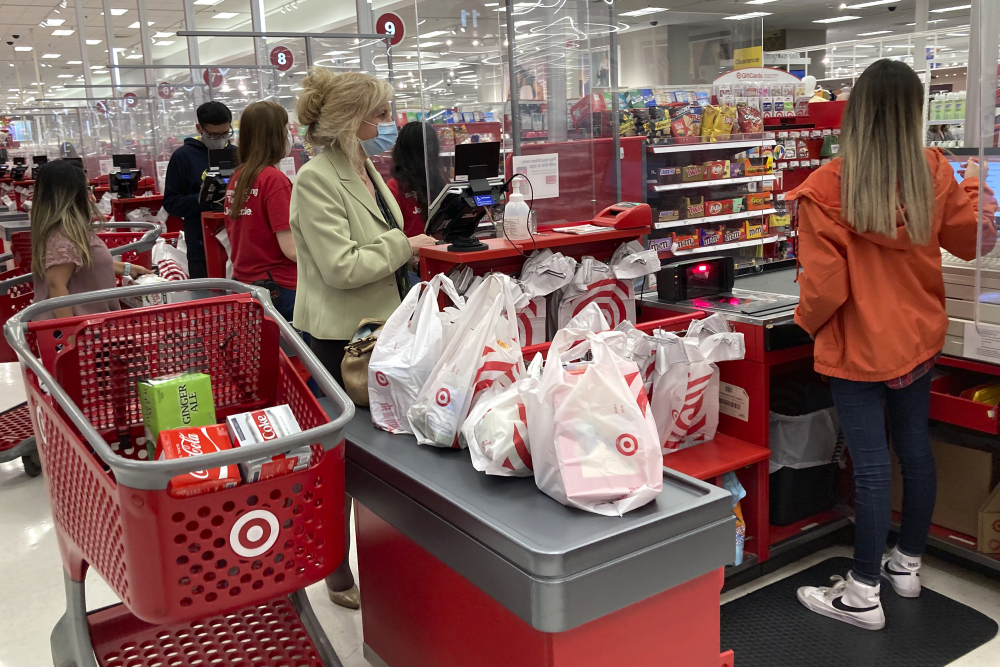 A customer wears a mask as she waits to get a receipt at a register in a Target store in Vernon Hills, Ill., Sunday, May 23. Retail sales fell in May, dragged down by a decline in auto sales, likely due to fewer cars being made amid a pandemic-related shortage of chips.